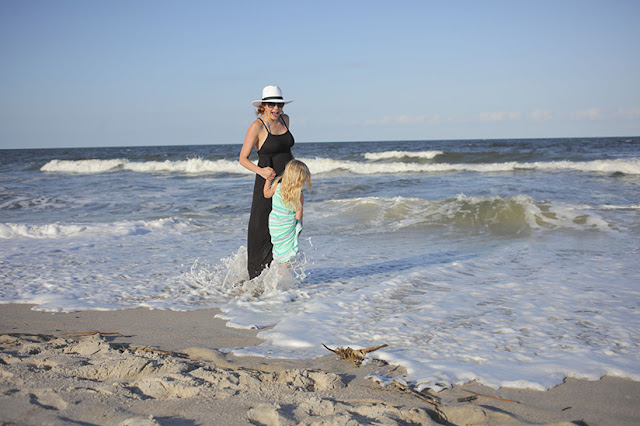 Amy West and daughter playing in the surf
