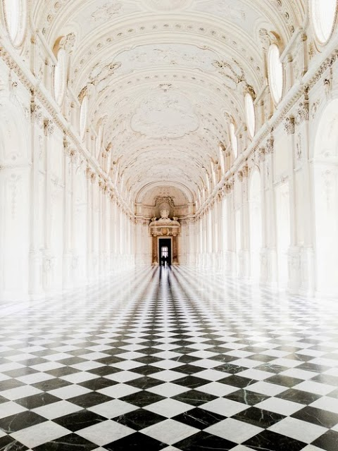 Black and white diagonal checkerboard floor in a grand hallway