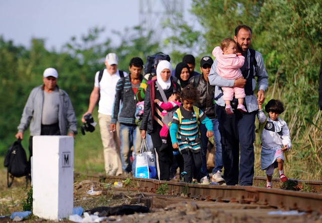 Imigrantes caminham sob trilhos na fronteira entre Sérvia e Hungria