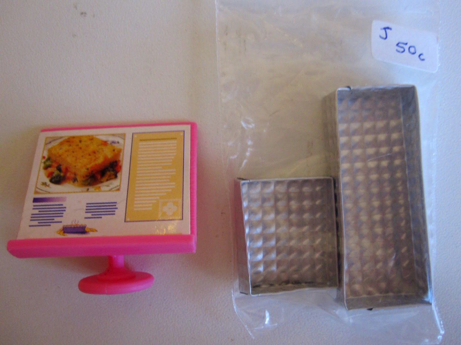 Pink plastic miniature menu board and bag containing two silver-coloured miniature trays. Bag is marked 'J 50c'