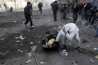 An Egyptian protester is helped away during clashes