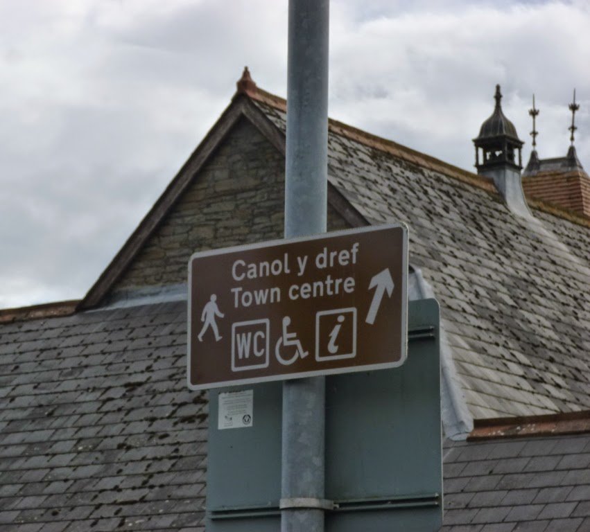 A brown sign pointing to Crickhowell's Canol y dref