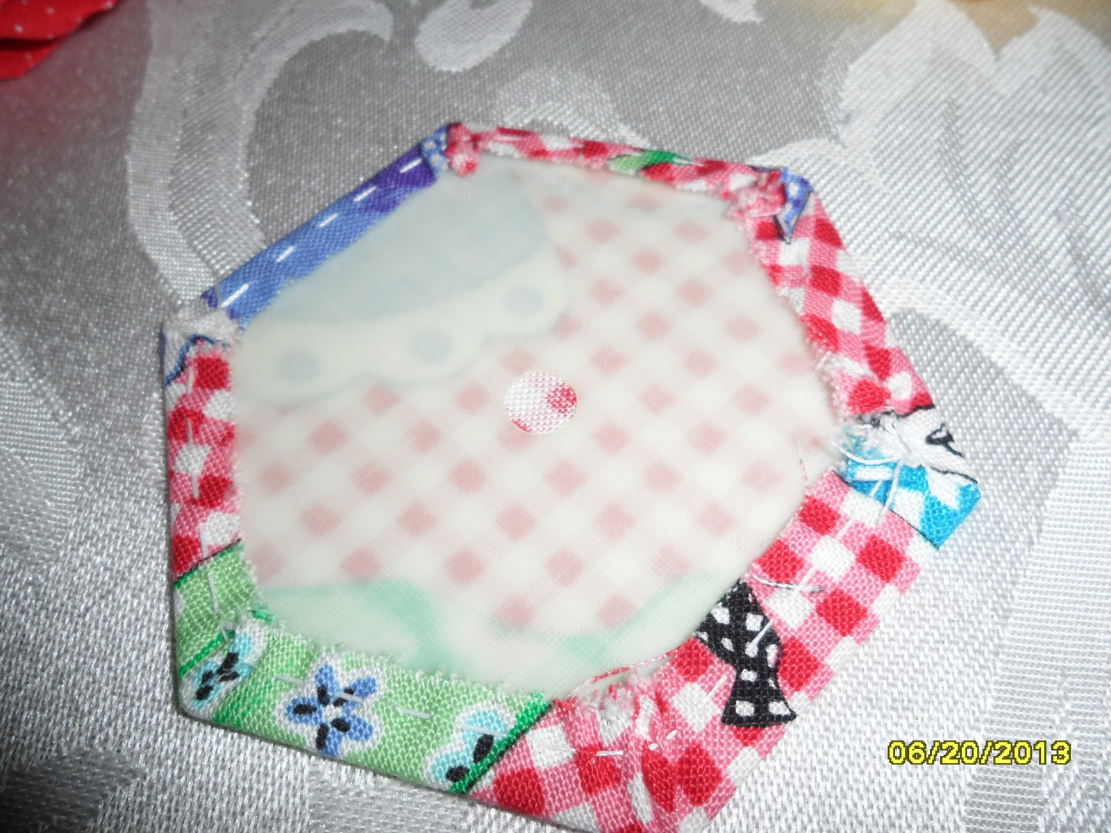 In sewtopia the hexagon english paper piecingplastic piecing the plastic template backing the fabric hexi a hole in the middle can be used to pin through to stabilize the fabric as you work and is used to pull the maxwellsz