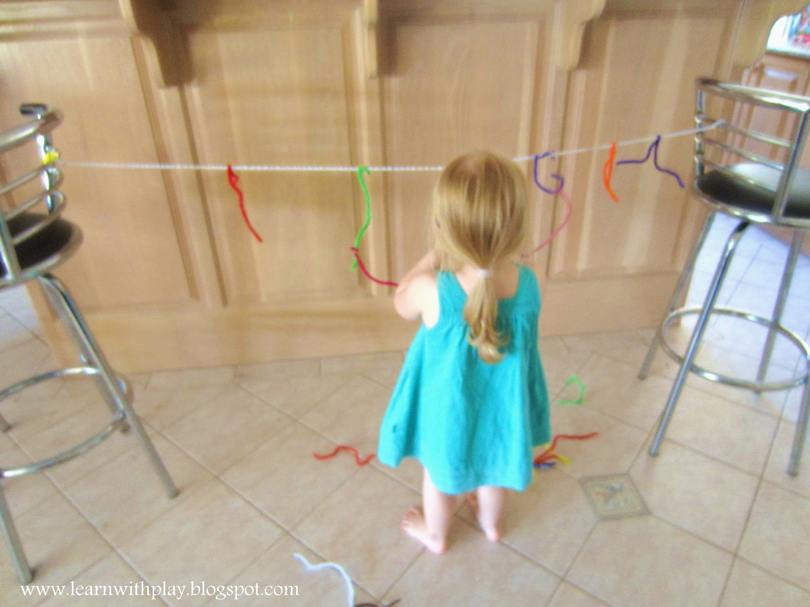 Learn with play at home fine motor pipe cleaners on a string for Motor skills for toddlers