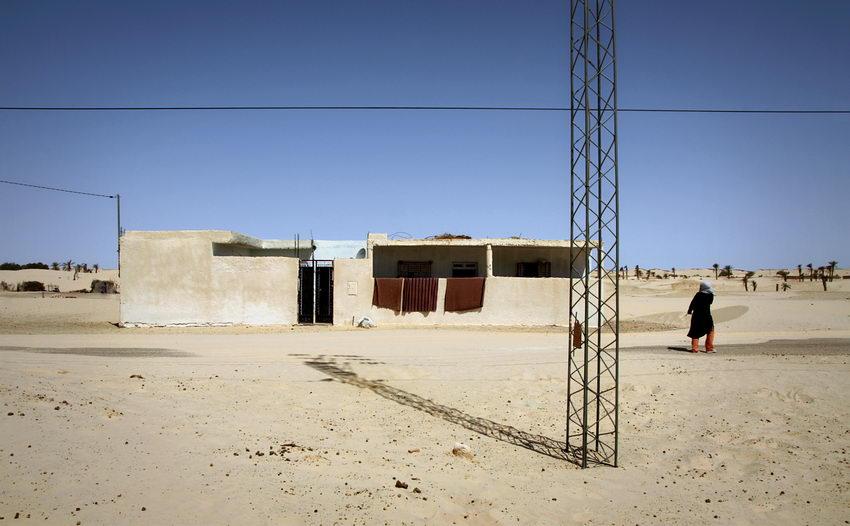 Foto de uma casa numa zona desértica. Um poste de electricidade em primeiro plano e uma pessoa a passar