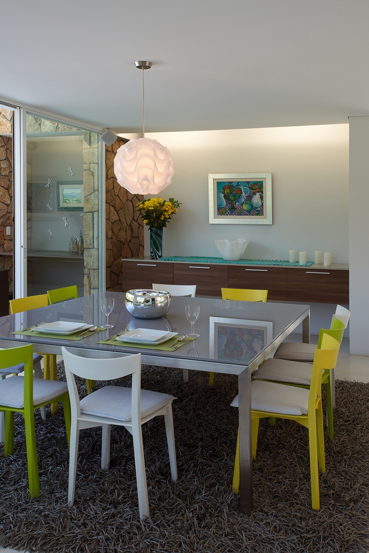 Dining table with yellow chairs in the Casa del Viento by A-oo1 Taller de Arquitectura