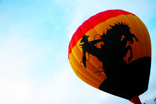 A hot air balloon with a cowboy design on it at the Colorado Balloon Classic.