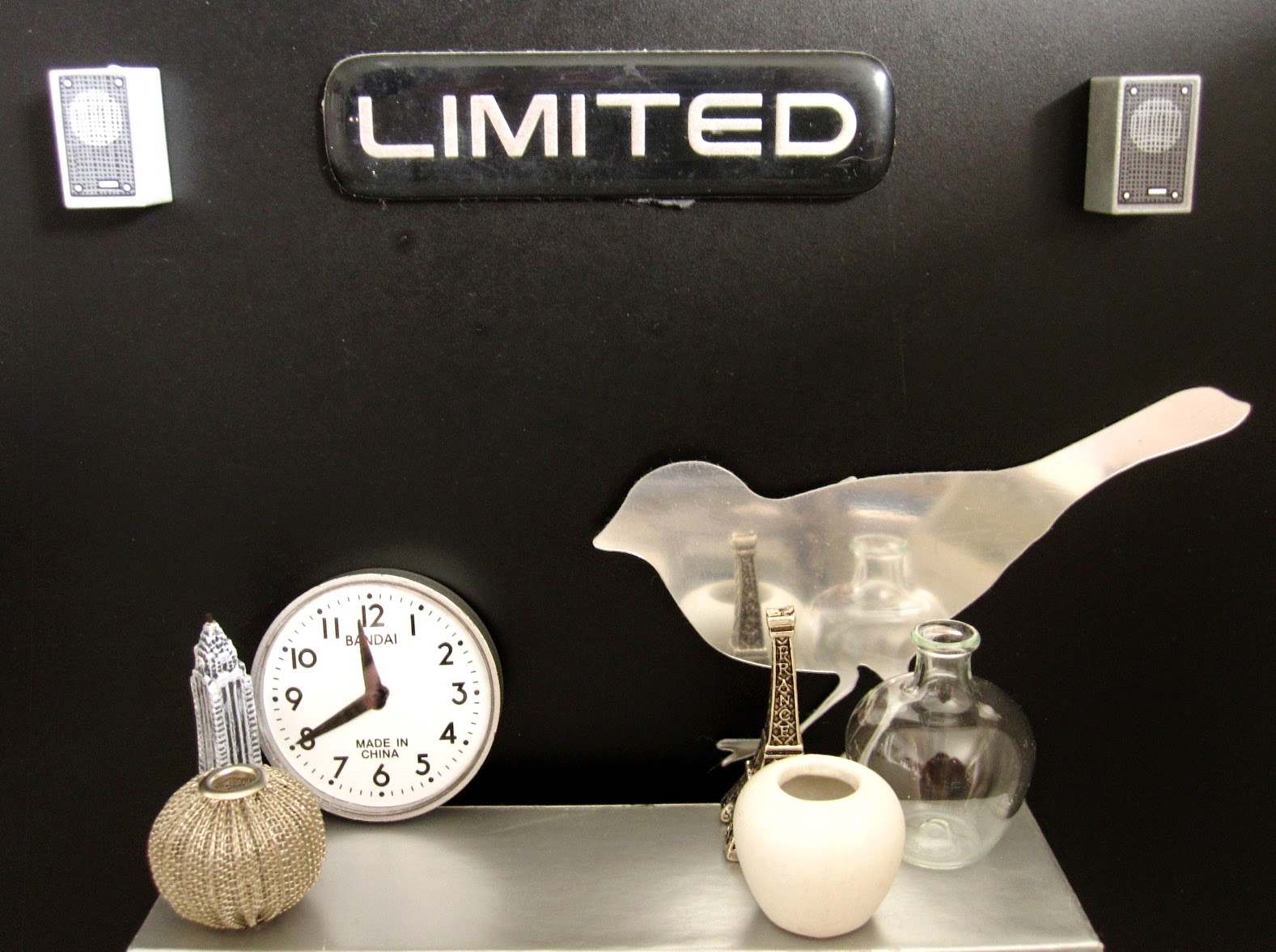 Modern dolls' house scene of a selection of grey, white and silver decoative items displayed on an industrial grey bench against a black wall. On the wall are to stereo speakers and a sign saying 'Limited'