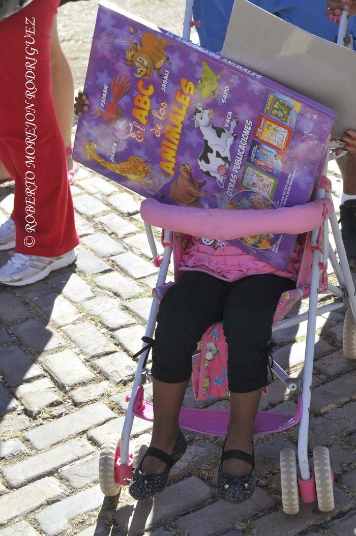 Una niña carga un enorme libro infantil durante su visita a la XXIII Feria Internacional del Libro Cuba 2014, en su sede principal, la Fortaleza San Carlos de la Cabaña, en La Habana, el 16 de febrero de 2014.
