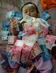 anak kecil sedang dikasih uang oleh orang tuanya