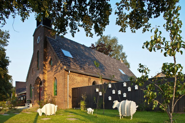 Picture of the church and sheep sculptures on the grass as seen from the street