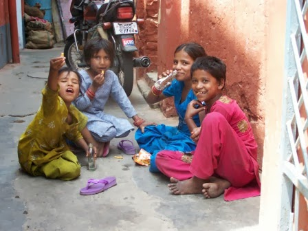 Children sitting on the floor in a daily backyard - waving to the camera