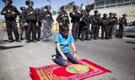 Bocah khusyuk sholat membelakangi Tentara Israel
