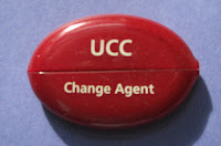 "oval, red plastic coin purse with the words ""UCC Change Agent"""