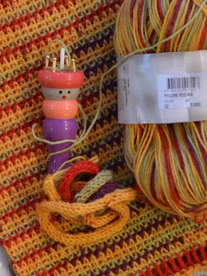 French knitting dolly and skein of yarn resting on top of the flattened striped bag.  A thread from the skein is attached to the pegs on the top of the knitting dolly. French knitted cord is coming out of the bottom of the knitting dolly and is coiled around itself in a bunch.