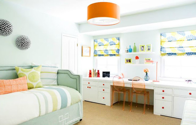 bedroom with an orange pendant light, mint green upholstered futon, wall length white desk with orange wire chairs with white cabinets with orange drawer pulls