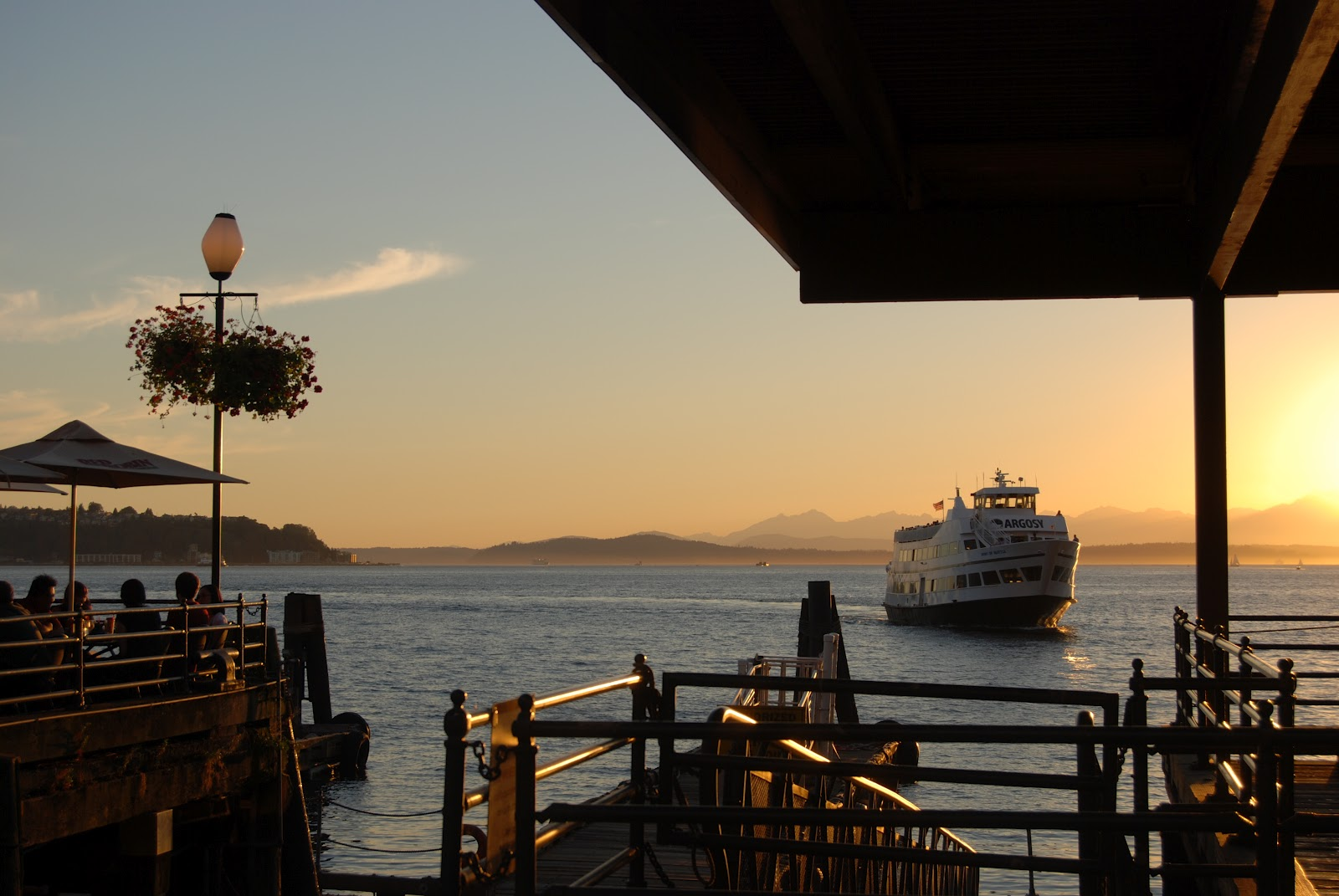 ferry makes its way back from across elliot bay while the sun drops