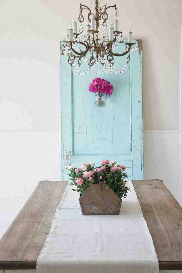 Stare, niebieskie drzwi oparte o białą ścianę. Drewniany stół rustykalny