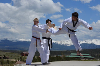 Martial arts black belt instructor breaking a board