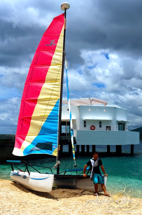 Yodi souvenir photo at the Bellarocca Resort Dock area on a boat with colorful sails.