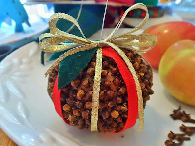 Apple covered with cloves, wrapped with pretty gold and red ribbon, with green velvet leaves and gold ribbon bow.