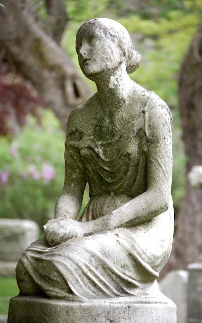 Forvitret kirkegårds-skulptur med siddende pige