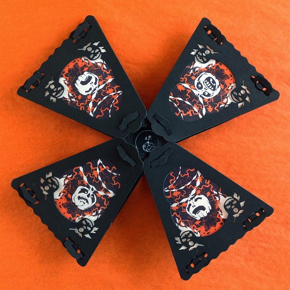Halloween pumpkin Jack O'Lanterns festooned with vines and crepe paper on orange and black paper lantern