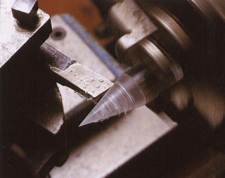 Set the angle of cut on the lathe at 75' and insert a round acrylic rod with a diameter of 5/8 inch into the chuck. Carefully turn a cone shape.