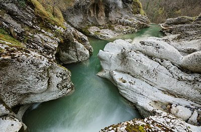 The green water of Fornant river running between white rocks