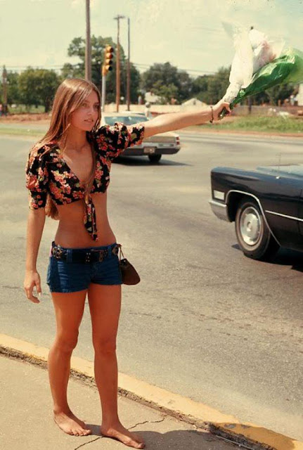 A woman sells flowers on the roadside of California in the early 1970s