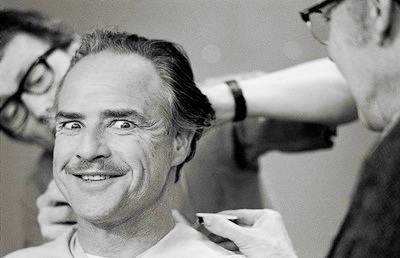 Marlon Brando making a funny face while having makeup applied for his role in The Godfather movieloversreviews.blogspot.com