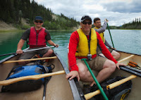 3 Men sitting on 3 separate Canadian Canoes