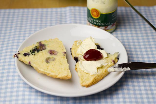 frisch gebackene Scones mit Blaubeeren, bestrichen mit Clotted Cream und Konfitüre