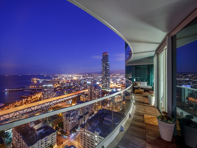 Picture of city lights and the bay at sunset as seen from the balcony of small duplex apartment