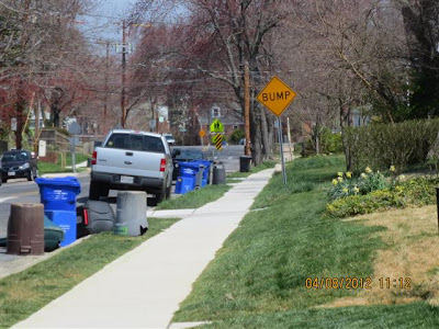 Street view of clear sidewalk, with trash cans and recycling containers along the curb.