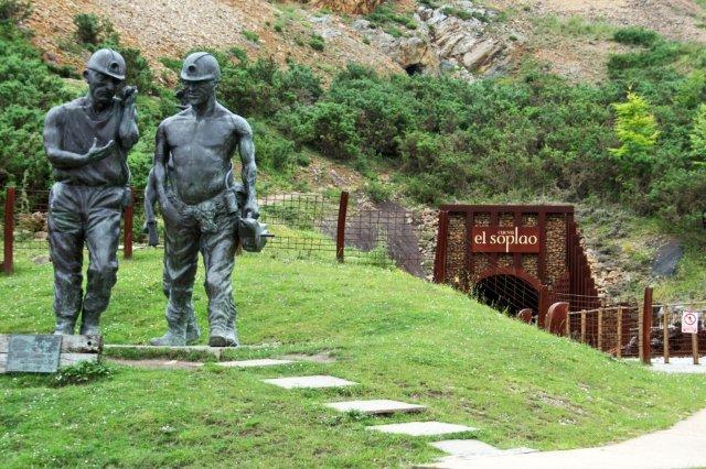 Estatua mineros y railes del tren minero en la Cueva El Soplao en Cantabria