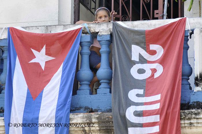 Una niña mira desde un balcón engalanado con una bandera cubana y otra del Movimiento 26 de Julio, en La Habana, Cuba, el 24 de julio de 2013.