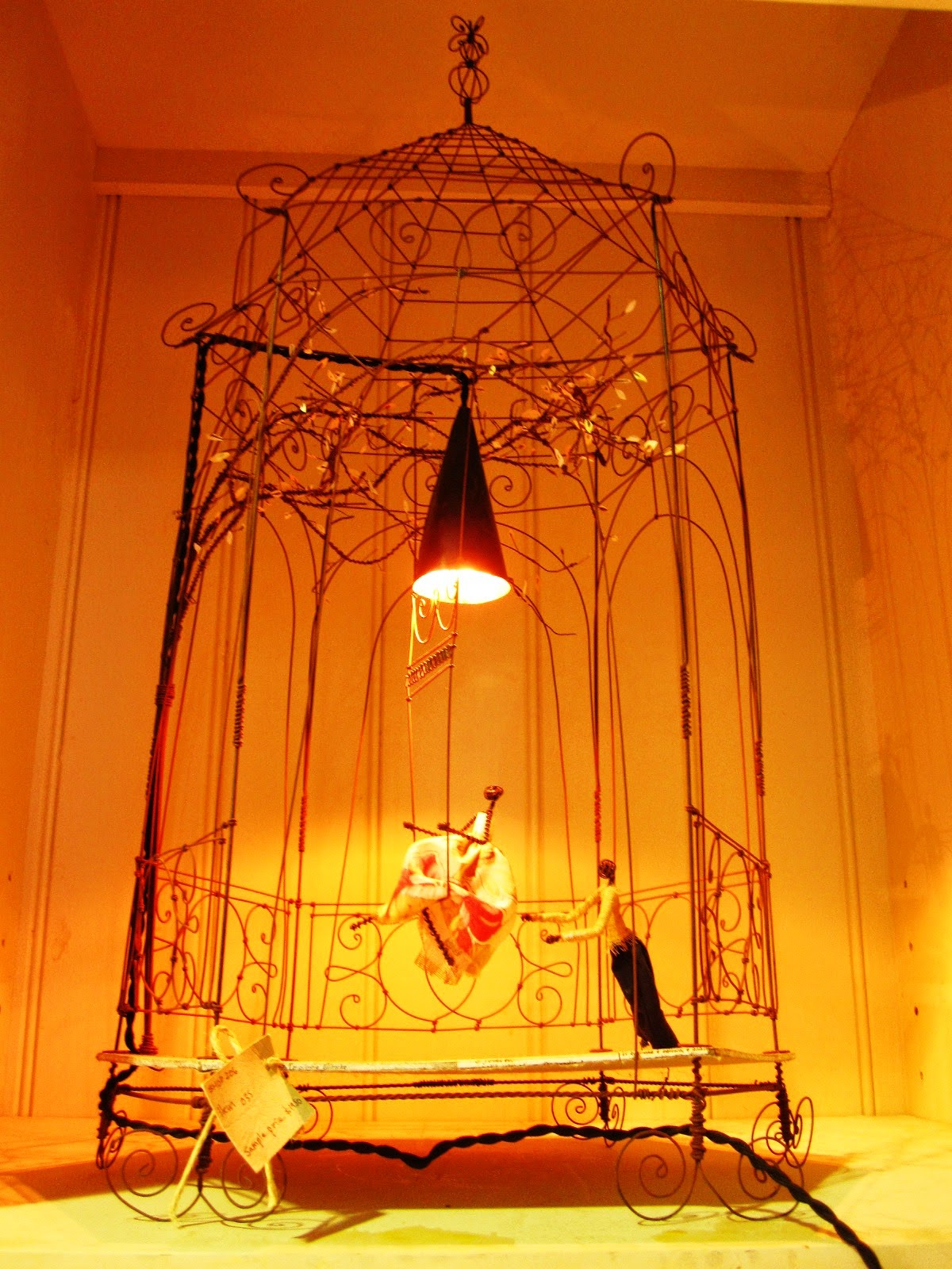 Vintage wire birdcage-shaped sculpture with wire swing and fabric dolls, used as the basis for a lamp.