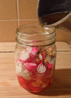 Brine Being Poured into Jar of Radishes