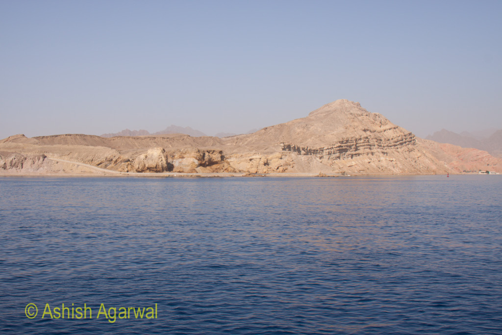 Blue water and limestone cliffs at the Red Sea off the shore of Sharm el Sheikh in Egypt