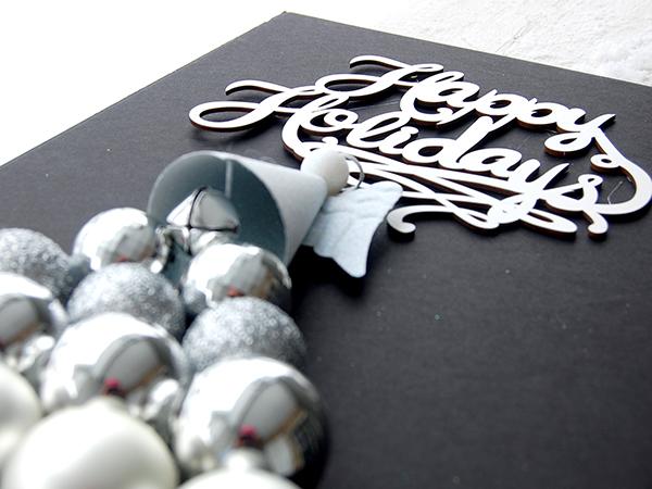 White Happy Holidays sign, white glitter ornament, silver ornament bulbls upclose