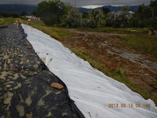 Plastic  sheeting placed on a dam crest and downstream slope to protect the dam from saturation and erosion due to overtopping