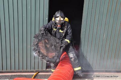 Un bombero con equipo de respiración autónomo extrae parte del material calcinado de una nave del polígono