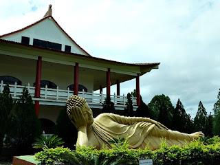 Estátua dourada de monge deitado em frente ao Templo Budista de Foz do Iguaçu.