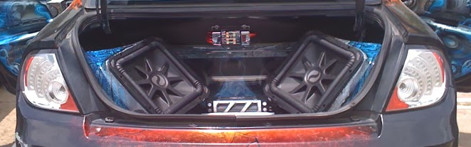 Photo image of an open trunk where the kicker woofers are installed facing backwards