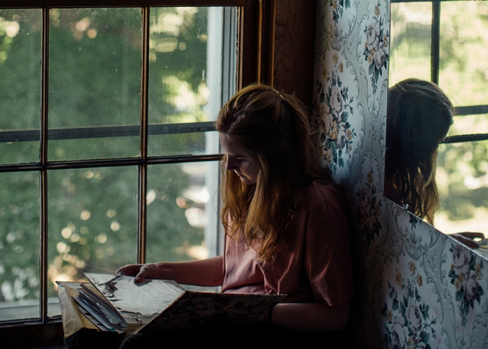 A girls sits in a window seat and reads her gratitude journal.