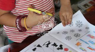 Szöveg: S ha elfáradunk a ceruzás tevékenységekben, akkor ollóval vágjuk ki a nekünk tetsző figurát. Kép: Közelkép egy ollós gyerekkézről, amint a füzetből keresgéli, hogy hópelyheket, kiszínezett gyertyákat vagy árnyakat vágjon ki.