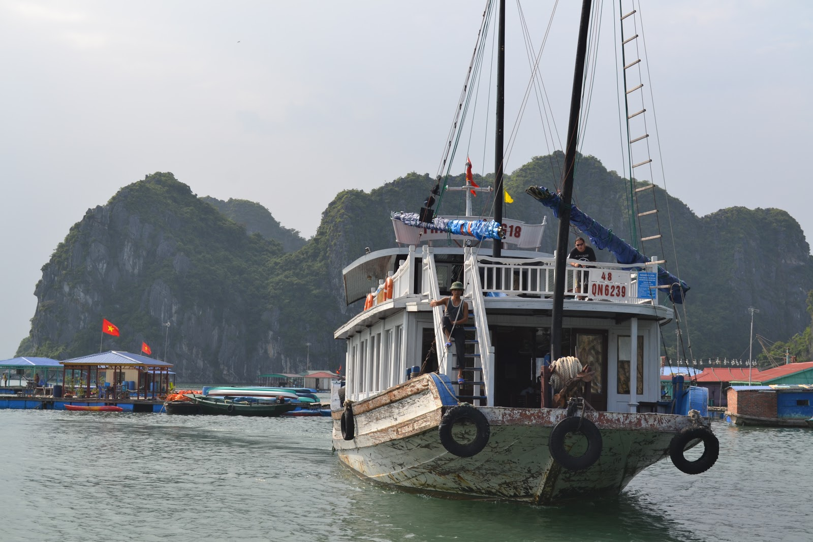 Anchored ferry near floating village , halong bay