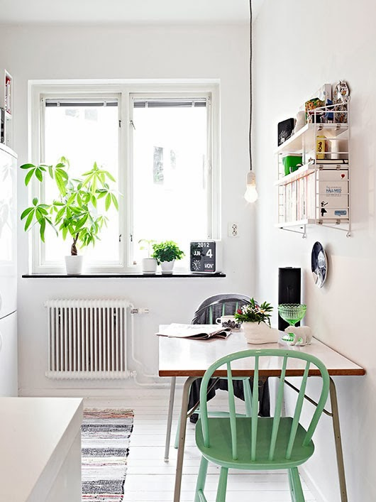 Cocina blanca con sillas verdes