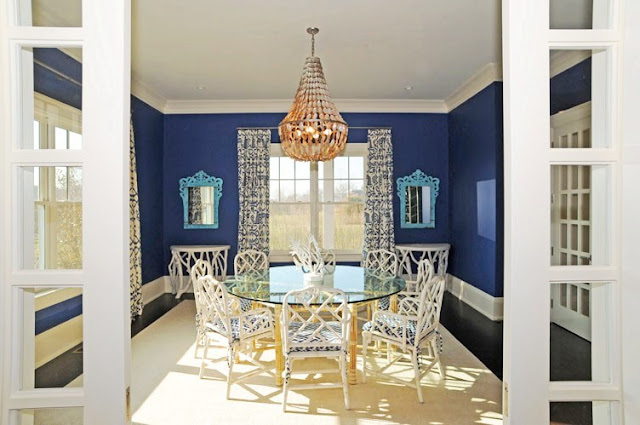 dining room with blue walls with white trim, a chandelier, french doors with blue and white curtains, dark wood floor, a round table with a glass top and white wood chairs with blue and white cushions